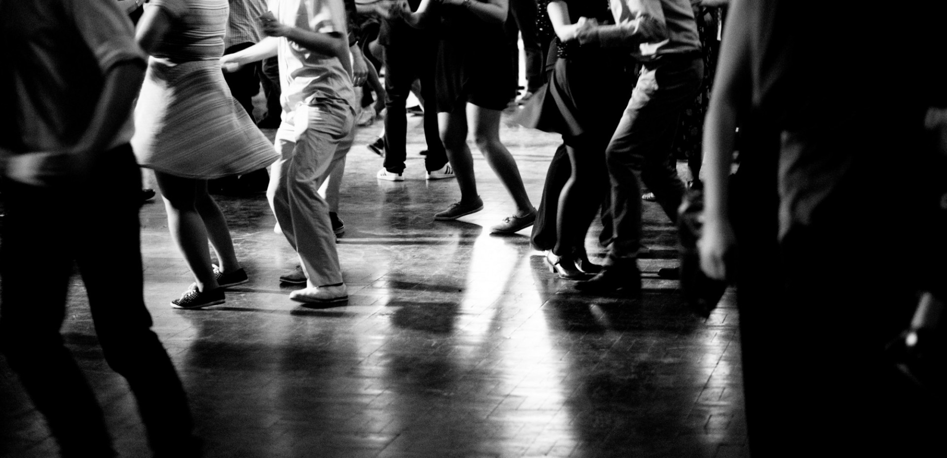 black and white image of people dancing on a dancefloor