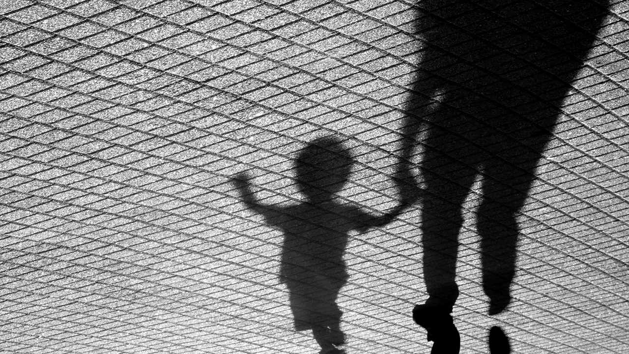 Silhouette of a parent holding a child's hand